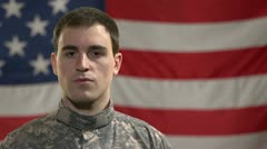 Caucasian male soldier standing in front of American flag - stock footage