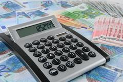 Calculator on euro banknotes Stock Photos