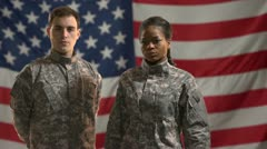 Male and female soldiers standing in front of American flag.  Stock Footage