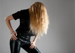Girl in leather pants showing up her long hair Stock Photos