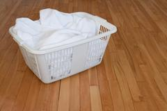 Laundry basket with white towels on wooden floor - stock photo