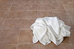 Creased white towels on ceramic floor - stock photo