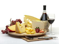 cheese still life on a wooden round tray - stock photo