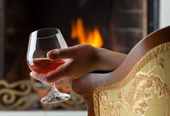 resting at the burning fireplace fire with a glass of cognac - stock photo