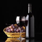 a bottle of red wine, glass and grapes - stock photo