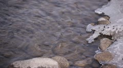 Rippling Clear Water  Next to Icy Rocky Shoreline - stock footage