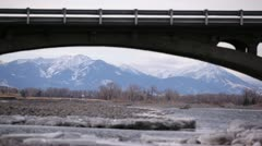 Bridge Over Rocky Stream With Mountaneous Backdrop Stock Footage