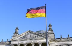 the german flag flying in front of the reichstag in berlin - stock photo