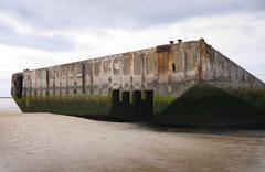 remains of artificial mulberry harbour at arromanches, france - stock photo
