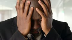 Upset African American businessman holding head in hands Stock Footage