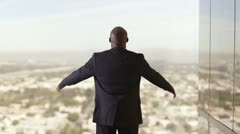 Rear view of African American businessman holding arms out wide and looking Stock Footage