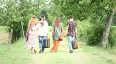 Hippie Group Walking on a Countryside Road Stock Footage