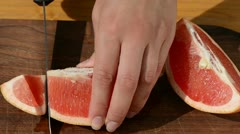 Hand slice fresh ripe grapefruit pomelo fruit into pieces Stock Footage