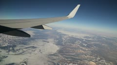 Airplane jet flying over snow mountain rocky window view - stock footage
