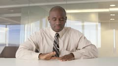 African American businessman listening to music at desk Stock Footage