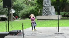 Young girl kid sing and dance on scene with microphone Stock Footage