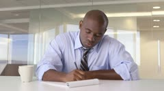 African American businessman working at desk throwing out paper Stock Footage