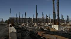 Charred Burnt Skeletal Remains of Industrial Building Disaster - pan - stock footage