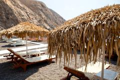 sunbeds in perissa, santorini, greece - stock photo