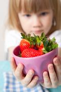 little girl with a bowl of strawberries - stock photo