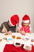 Girls decorating gingerbread cookies Stock Photos