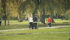 Family walk through the park with baby in the pram Stock Footage