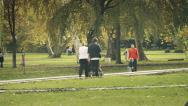 Stock Video Footage of Family walk through the park with baby in the pram