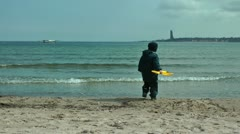 Happy little boy on the beach playing Stock Footage