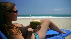 Girl drinking coconut milk on the beach Stock Footage
