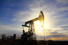 Stock Photo of working oil pump at sunset