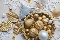 Golden nuts, shell, beads and white ball lying in the basket on the christmas ba Stock Photos