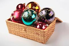 Christmas tree decorations in the basket on a white background Stock Photos