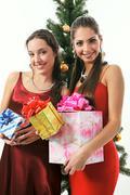 Kaksi nuorta kaunis nainen punaisessa mekossa pitävät esittelee lähellä joulua t Kuvituskuvat