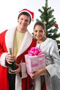 portrait of young couple in new year's suits on the background of fir-tree - stock photo