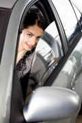 Portrait of vivid brunette looking with interest through the window of her car Stock Photos