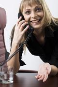 smiling expressive blond businesswoman talking by her phone - stock photo