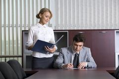 Smart secretary is giving documents to her boss for signing Stock Photos
