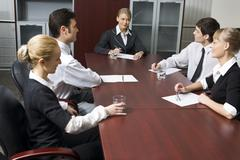 Team of successful business people are sitting at the table and discussing Stock Photos