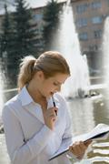 portrait of pretty business woman reading an interesting agreement in the park - stock photo