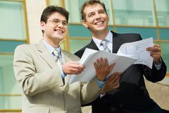 Two businesspeople holding papers looking towards and business center with glass Stock Photos