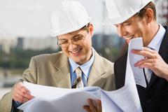 confident architect  is proposing a new plan of building to his chief - stock photo