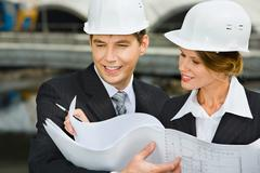 Confident female worker is showing a architectural plan to her chief Stock Photos