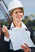 portrait of beautiful engineer holding architectural project and pen - stock photo