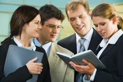Stock Photo of confident smiling professionals are discussing  a conditions of contract on the