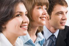 portrait of three young smiling businesspeople - stock photo
