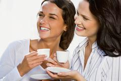 Portrait of two business women holding cups of coffee in their hands Stock Photos