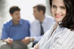 portrait of successful young woman on the background of two businesspeople - stock photo