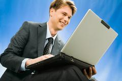 successful young smiling businessman sees a plan the decision of a question in t - stock photo