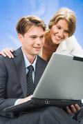 Stock Photo of young woman looks in the laptop with her colleague