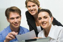 portrait of three business people looking at camera in a working environment - stock photo